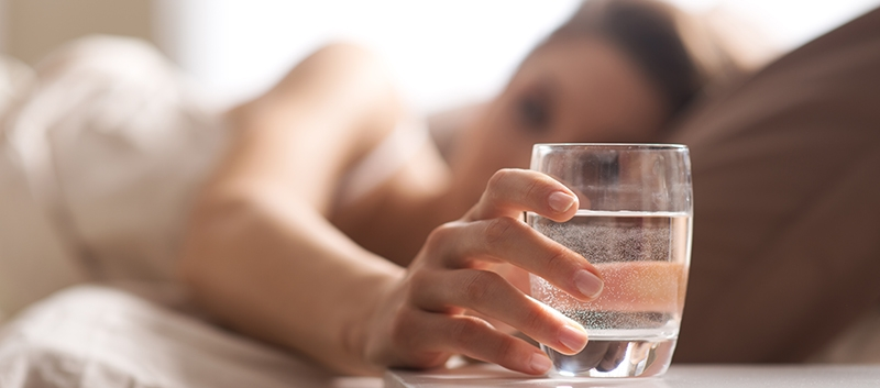 woman drinking a glass of salty water