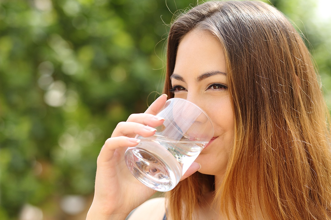 Happy woman drinking water at the right pH